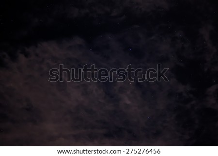 Several stars in the black sky of a cloudy night - stock photo