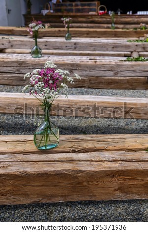 several tables and benches made of old beams with flowers on it - stock photo