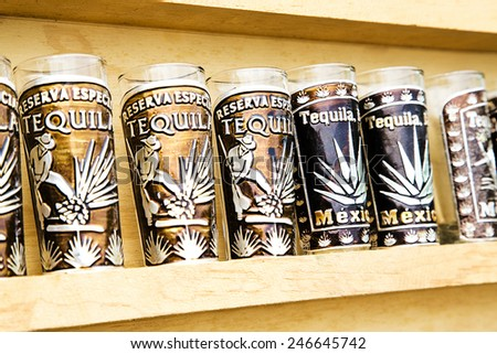 Several tequila souvenir glass in wood cabinet - stock photo