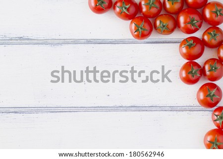 Several tomatoes on a white wooden table - stock photo