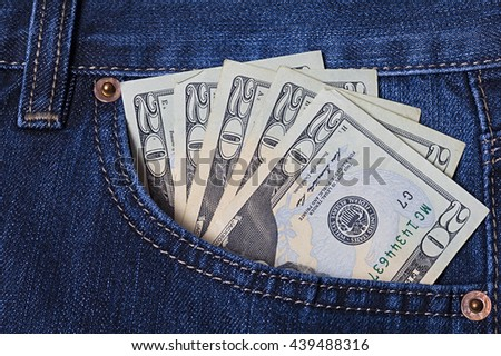 Several twenty dollar bills in the pocket of a pair of jeans