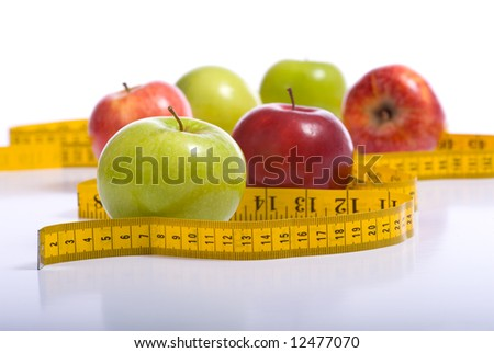 Several varieties of fresh apples with a yellow tape measure on a white background.  Dieting or eating healthy concept