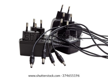 Several various battery chargers with various connectors for mobile phone and other gadgets on a light background