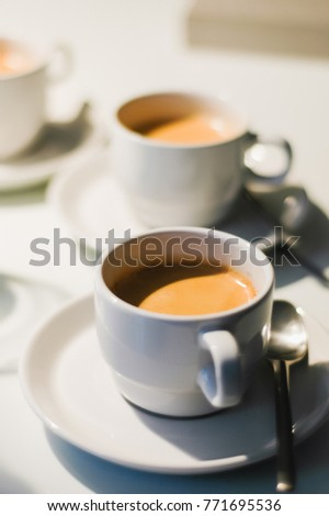 Several white coffee cups with freshly brewed coffee with a beautiful cream served in vintage 90s tableware on white conference table at a meeting