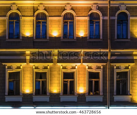 Several windows in a row on night illuminated facade of urban office building front view, St. Petersburg, Russia