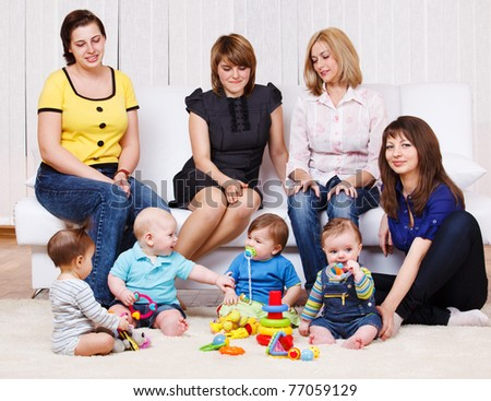 Several young women and their kids playing - stock photo