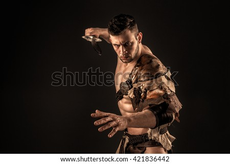 Severe barbarian in leather costume with sword - stock photo