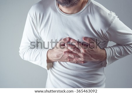 Severe heartache, man suffering from chest pain, having heart attack or painful cramps, pressing on chest with painful expression. - stock photo