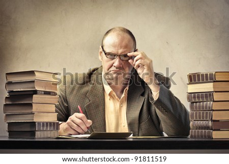Severe teacher using a calculator - stock photo