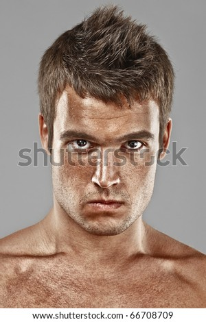 Severe young man lours, on gray background. - stock photo