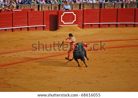 "SEVILLE - APRIL 30:  A bull chases Bullfighter David Fandila ""El Fandi"" as he fights for a sold out crowd at the Plaza de Toros de Sevilla April 30, 2009 in Seville, Spain. - stock photo"
