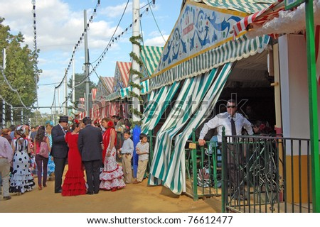 SEVILLE - APRIL 28: A guard stands outside a casita as the crowds gather to celebrate  during the Feria de Abril on April 28, 2009 in Seville, Spain. - stock photo