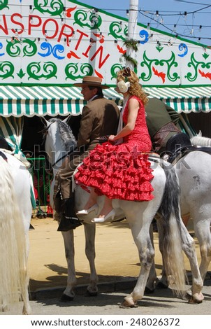 SEVILLE, SPAIN - APRIL 12, 2008 - Spanish couple in traditional dress sitting on a horse with Casitas to the rear at the Seville Fair, Seville, Seville Province, Andalusia, Spain, April 12, 2008. - stock photo