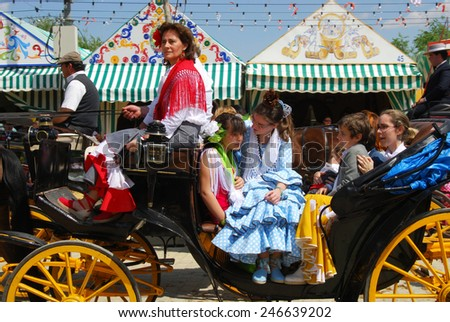 SEVILLE, SPAIN - APRIL 12, 2008 - Spanish family in traditional dress travelling in a horse drawn carriage at the Seville Fair, Seville, Andalusia, Spain, Western Europe, April 12, 2008. - stock photo