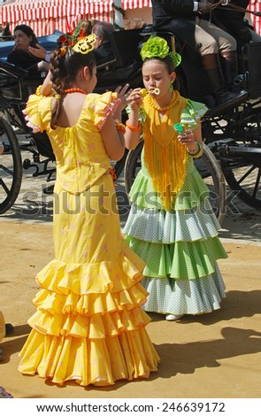 SEVILLE, SPAIN - APRIL 12, 2008 - Spanish girls in traditional dress blowing bubbles at the Seville Fair, Seville, Seville Province, Andalusia, Spain, Western Europe, April 12, 2008. - stock photo