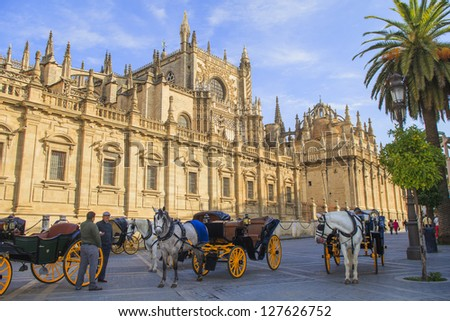 SEVILLE, SPAIN-OCT 29: Horse drawn carriages with guides in front of the Cathedral on Oct 29, 2012. About a hundred carriages make tours around the center of Seville and the famous Maria Luisa Park - stock photo