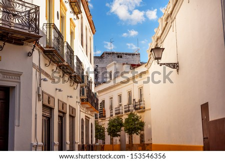 SEVILLE, SPAIN--OCTOBER 20, 2012 Matador Painting in Narrow Streets of Seville, Street with Lamp, Balconies, Yellow White Andalusia Spain on October 20, 2012.     - stock photo