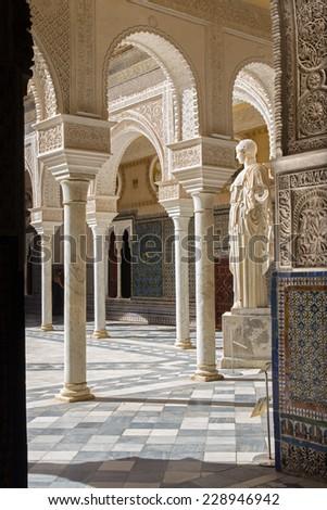 SEVILLE, SPAIN - OCTOBER 28, 2014: The Courtyard of Casa de Pilatos and the copy of antique statue of Pallas Pacifera.  - stock photo