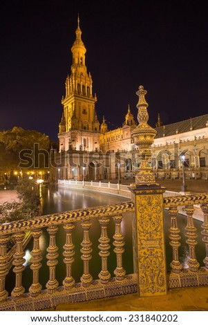 Seville - The ceramic tiled bridge one tower on Plaza de Espana square designed by Anibal Gonzalez (1920s) in Art Deco and Neo-Mudejar style at night. - stock photo