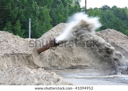 sewage flowing from a pipe in the river - stock photo
