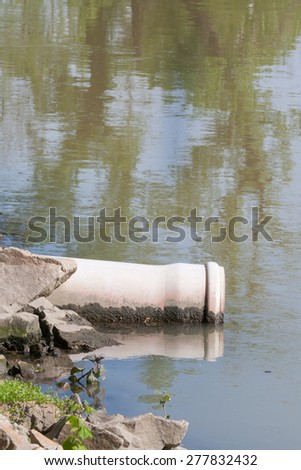 sewage pipe polluting the water - stock photo