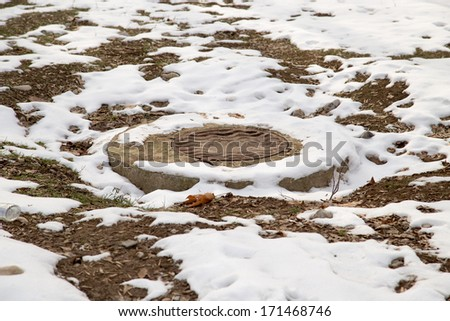 sewage pit in the snow - stock photo