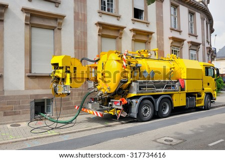 Sewage truck on city street in working process to clean up sewerage overflows, cleaning pipelines and potential pollution issues from an modern building. - stock photo