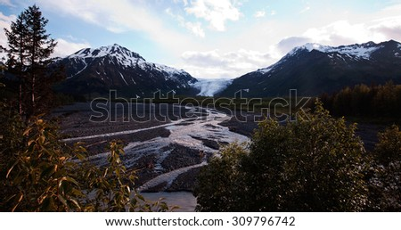 Seward,Alaska: Exit Glacier ice is slowly melting down. The resulting water forms a river flowing through the rock and nurturing small plants. - stock photo