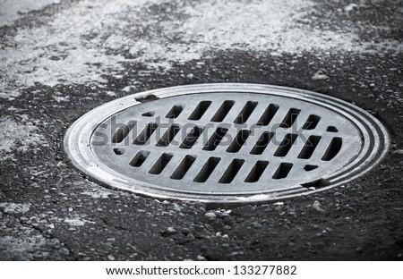 Sewer manhole on the urban asphalt road. Closeup photo - stock photo