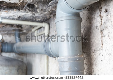Sewer pipes in home basement. System of gray sanitary pipes in old house.