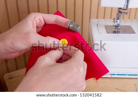 Sewing a button onto red fabric with sewing machine in background - stock photo