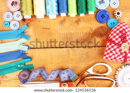 Sewing accessories and fabric on wooden table close-up - stock photo
