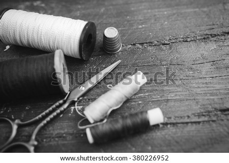 Sewing accessories: bobbins of thread, scissors, needle, thimble on wooden table. Black and white photo. Tailoring and sewing concept. - stock photo