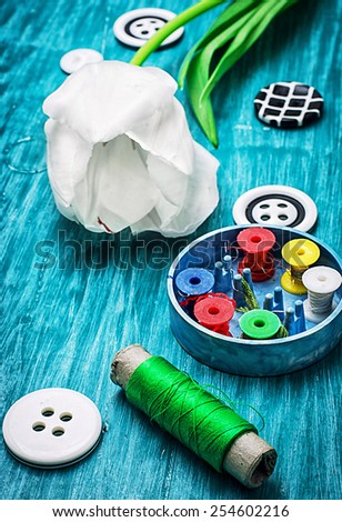 sewing accessories from threads and buttons on the background of white tulips - stock photo