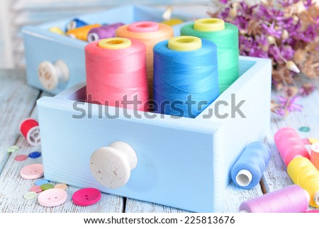 Sewing Accessories in wooden boxes on table close-up - stock photo