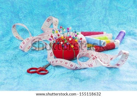 Sewing Accessories on fabric in blue color - stock photo