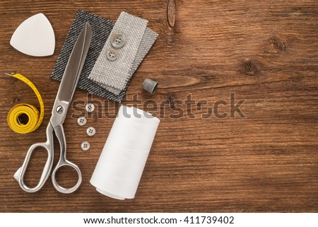 Sewing accessories on wooden background - stock photo