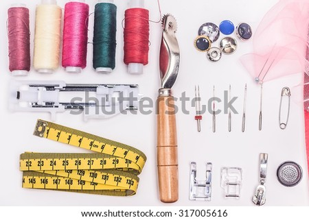 sewing accessories: thimble, thread, bobbin, foot, measure tape, button,textile, needle on white background - stock photo