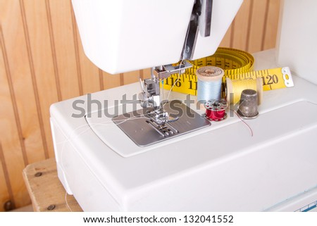 Sewing and sewing machine supplies, with measuring tape, thread, bobbin and thimble - stock photo