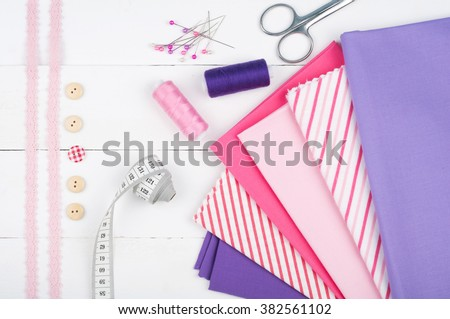 Sewing background. Cotton fabrics, spools of thread, scissors, buttons, measuring tape, sewing supplies. Accessories for sewing on white wooden background. Set for needlework top view - stock photo