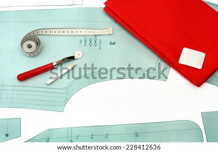 Sewing background. Sewing accessories and fabric on a paper pattern. - stock photo