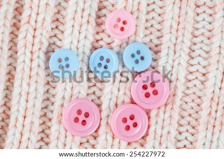 Sewing Buttons on a knitting background  - stock photo