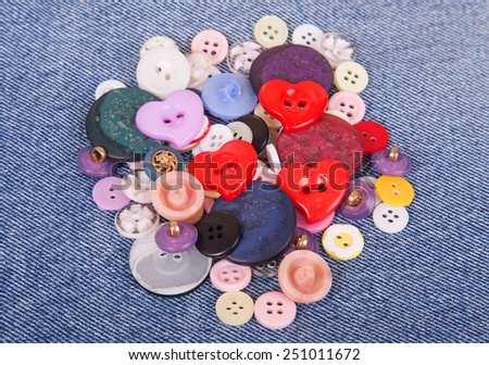 Sewing color buttons on denim jeans background - stock photo