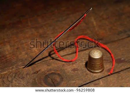 Sewing concept.Closeup of thimble and needle with thread on wooden background - stock photo