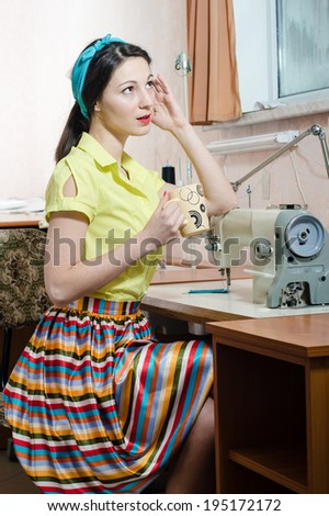 sewing in workshop beautiful brunette young woman pinup girl with red lips and nails in yellow dress blue ribbon on her head holding cup drinking tea & looking at window closeup portrait image