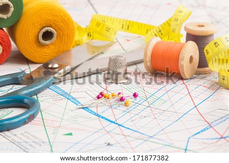 Sewing items background with old scissors, thread spools and tape measure