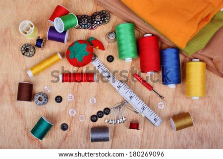 Sewing items: buttons, colorful fabrics, material, measuring tape, bobbins, buttons, cloth, safety pins, needles, pincushion, thimble, spools of thread - stock photo