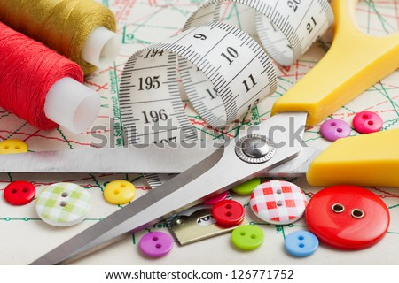 Sewing items: buttons, colorful fabrics, scissors, measuring tape, thimble, spools of thread on sewing pattern - stock photo