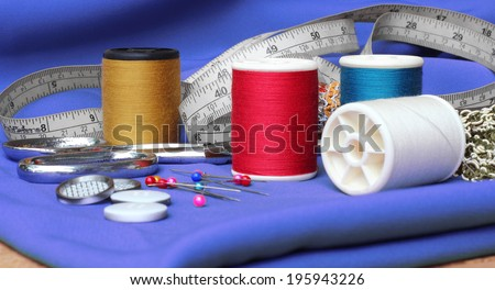Sewing items: buttons, material, measuring tape, bobbins, buttons, cloth, safety pins, needles, spools of thread,  scissors, lace