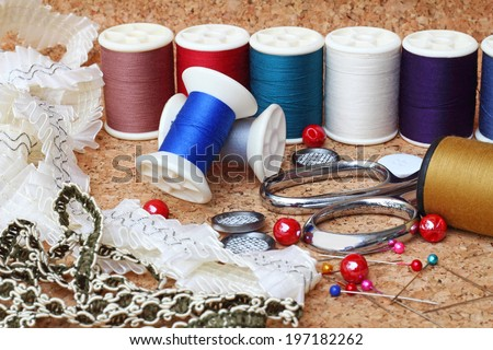 Sewing items: buttons, material, measuring tape, bobbins, buttons, cloth, safety pins, needles, spools of thread, scissors, lace - stock photo